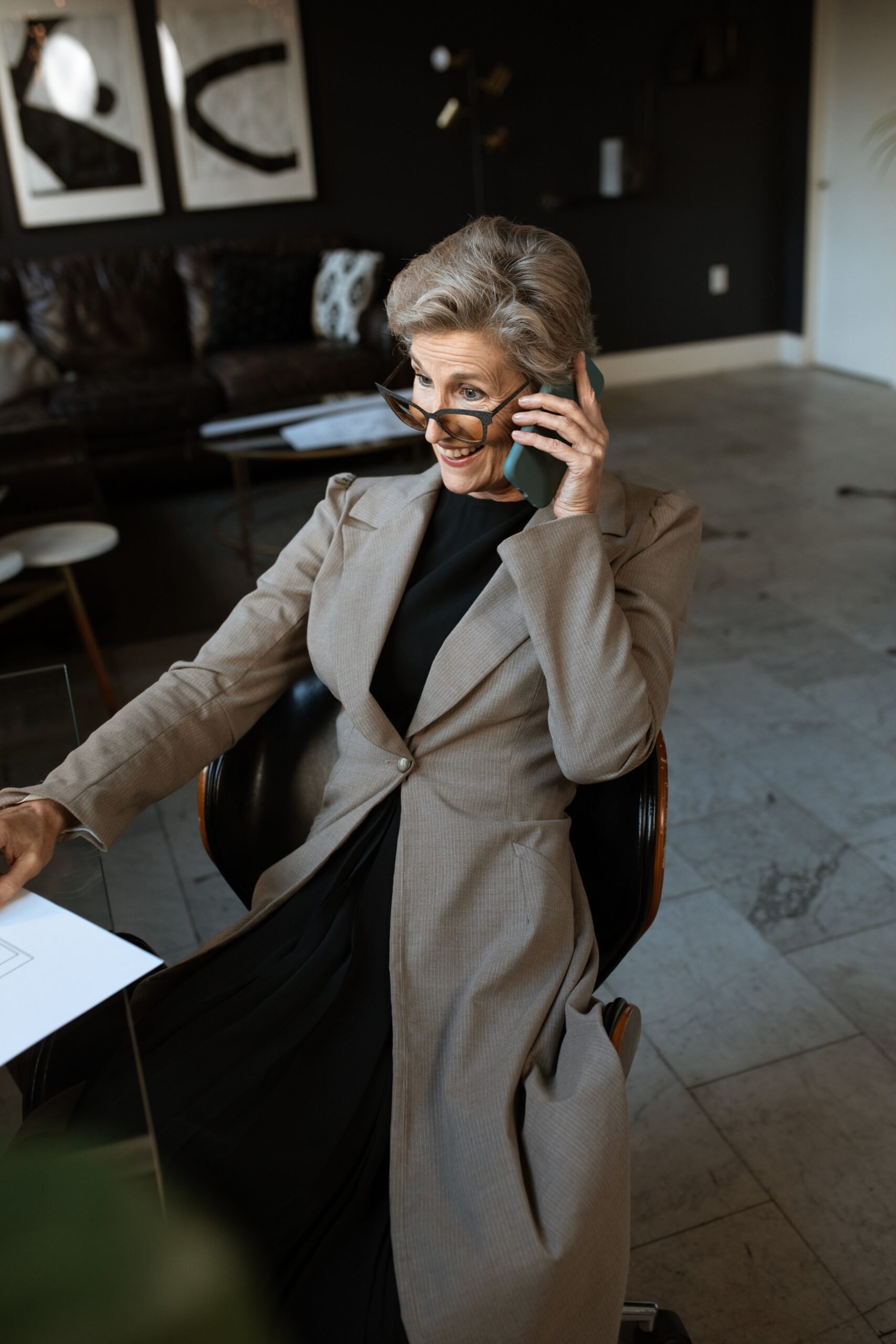 Professional woman on phone smiling at desk with papers.